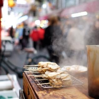 The aroma of grilled seafood permeates Kuromon Ichiba Market.